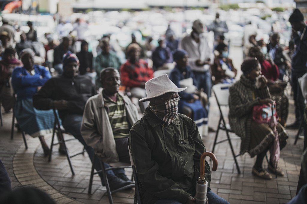 An elderly man at a SASSA pay-point in Soweto covers his mouth while queuing.