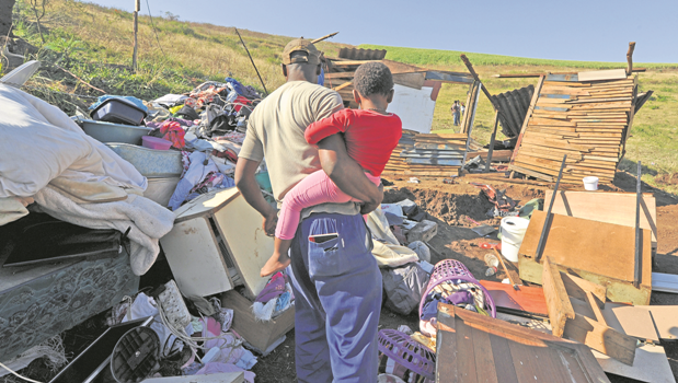 A man carries his daughter as he searches through their belongings from his demolished house after Msunduzi municipal workers tore down informal houses in Tamboville on Tuesday.