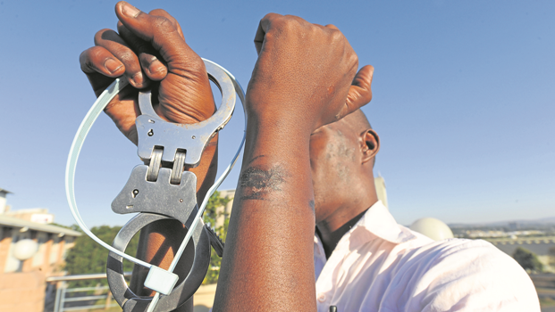 Mxolisi Zwane (34) holds the handcuffs and cable ties he alleges were used by a local pastor and his son who assaulted and wrongfully accused him of stealing from the church.