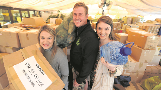 Jessica Campbell (left), Tim de la Hey and Kerri Holder are surrounded by boxes of supplies headed to Knysna after locals responded to their social media plea for donations for fire victims at Aintree Lodge.