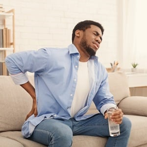 Young african-american man with back pain, pressin