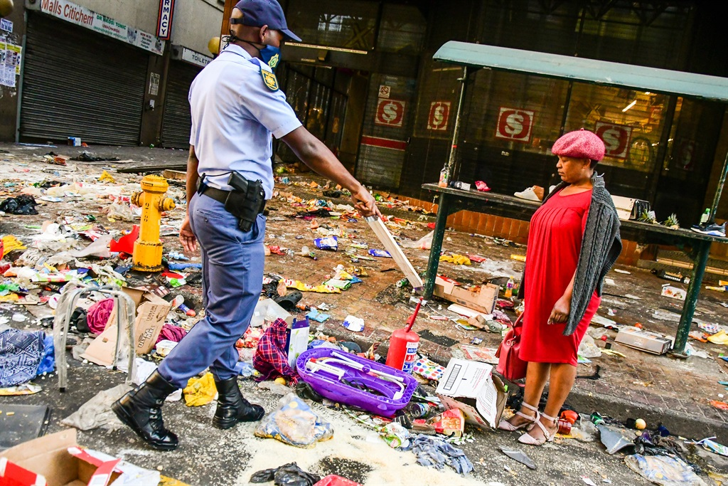 A police officer and civilian woman outside Shoprite in the Durban CBD on July 12, 2021 amid civil unrest and looting following the 'Free Jacob Zuma' protests. Photo by Gallo Images/ Darren Stewart