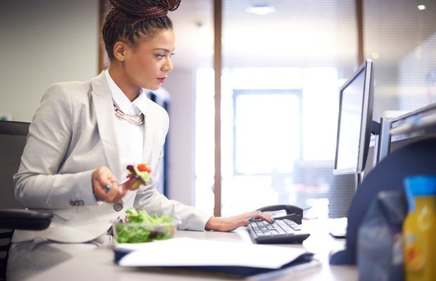 woman having lunch at her desk while working