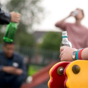 Teenagers drinking in a park.
