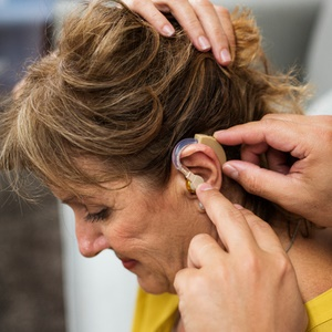 woman having her hearing aid inserted by doctor