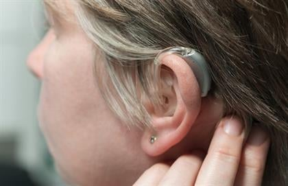 woman wearing her hearing aid
