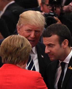 US President Donald Trump talks to German Chancellor Angela Merkel and French President Emmanuel Macron. (Patrik Stollarz, AFP)