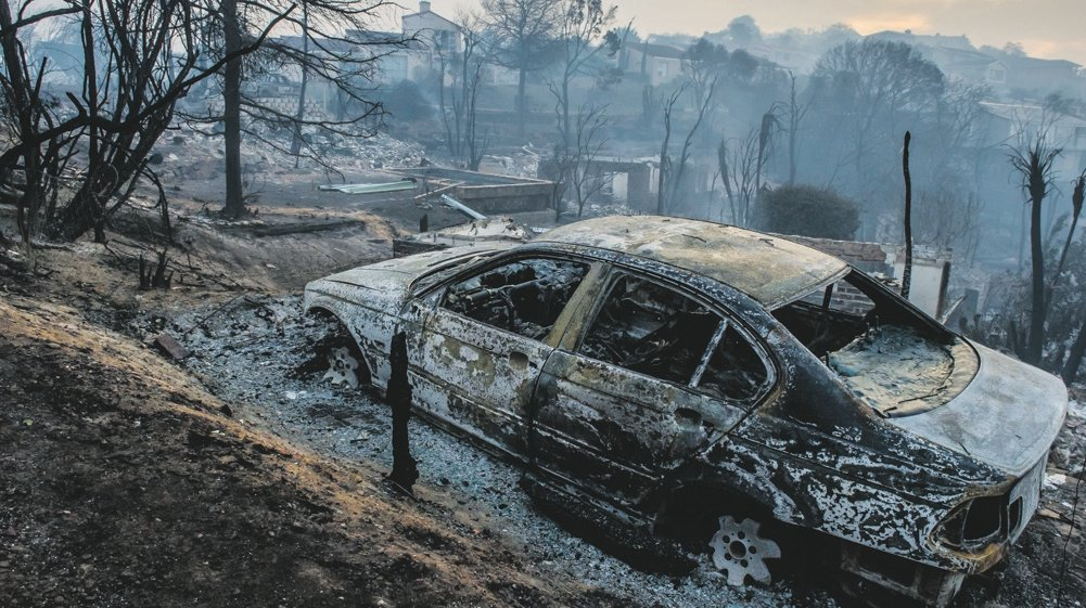 A burnt-out car and the ruins of buildings can be seen after the devastating fires in Knysna last month. Picture: Deon Raath