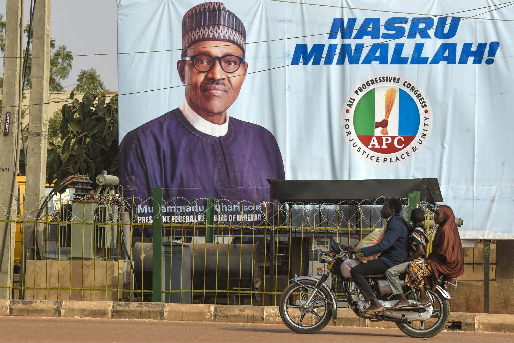 A motorcyclist taxi rides past a campaign poster of candidate of the ruling All Progressives Congress (APC) party, President Mohammadu Buhari in his native Daura Town, Katsina State on February 16, 2019.