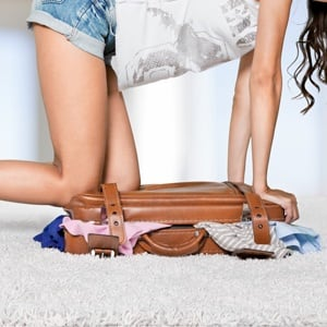 woman-trying-to-close-over-stuffed-bag