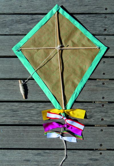 Finished kite with ribbons on wooden deck