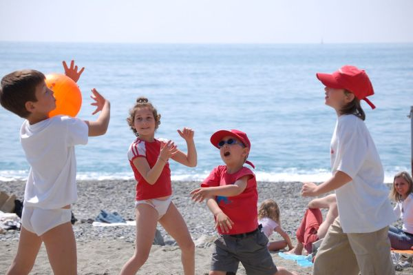 Kids playing on the beach with a ball