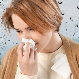 Woman with flu virus blows nose