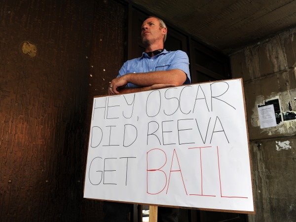 A man with a placard stands at the entrance of the Pretoria Magistrate's Court on Thursday, 21 February 2013 where paralympian Oscar Pistorius applied for bail. PHOTO: Werner Beukes/SAPA