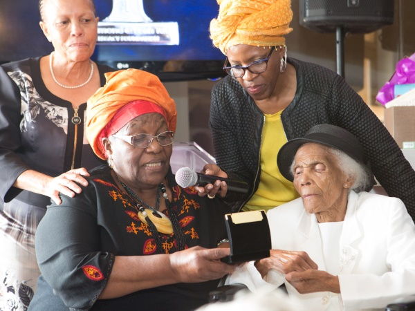 Leah presents Ethel Liesa with her award. In the background are Ethel's daughter, Mpho Mguli, and Leah's daughter, Reverend Canon Mpho Tutu. PHOTO: Misha Jordaan