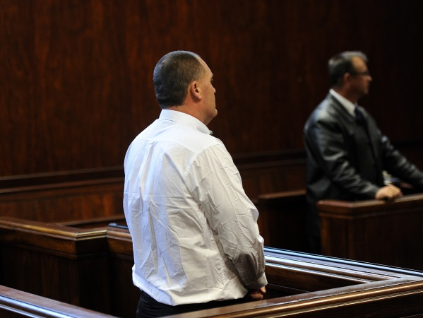 A man accused of abusing his wife and five children appears in the Springs Magistrate's Court on Wednesday, 4 June 2014. Investigating officer Rudolf Jansen (seen in the background)  told the court of the torture and assault the children -- aged between two and 16 -- had allegedly been put through by their father. The accused, who may not be named to protect the identity of his wife and children, faces charges of assault and kidnapping.Further charges, including one of rape, were expected to be brought against him after allegations that he had forcefully had sex with his wife. The Springs man was arrested last month after his son fled the house and sought help from neighbours.Picture: Werner Beukes/SAPA