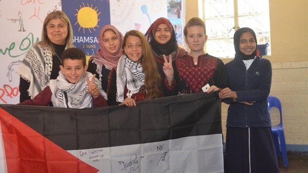 (From left) Director of Shamsaan, Nadia Meer, Muhammad Nawajah (13), Azwemah Thokna (14), Janna Jihad (11), Salsabil Khan (14), Ahed Tamini (16) and Husnaa Essop (12) stand with the Shamsaan story board banner with the stories of Palestinian children.