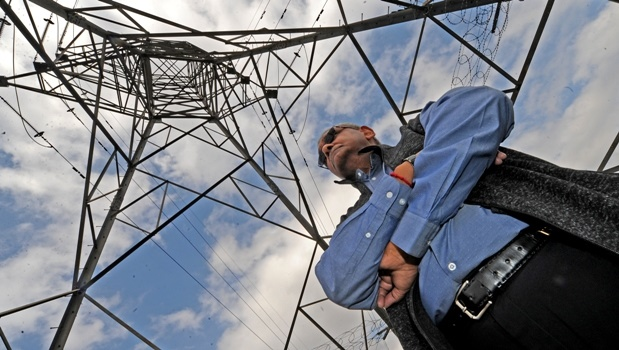 Community activist Jay Jugwanth stands under one of the electricity pylons near the Northdale power station on Monday. Msunduzi Municipality has reallocated R2 million — meant for upgrade of two sub-stations — to upgrade the municipal  offices.