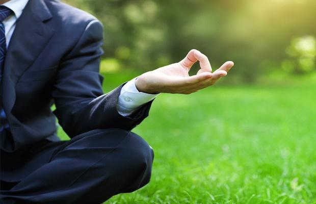 man in suit meditating in park