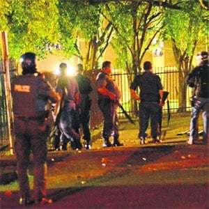 Police watch the gates to a residence at the Pietermaritzburg UKZN campus. (Chelsea Pieterse, The Witness)