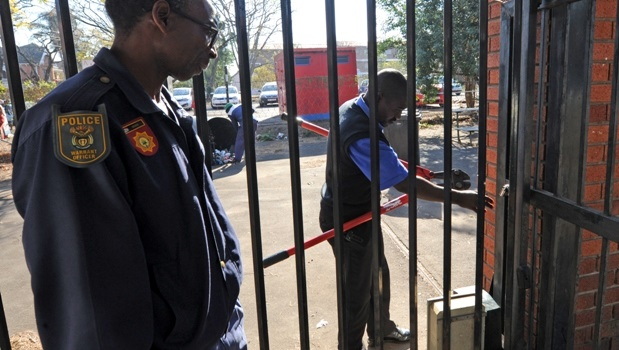 A policeman watches a FET College security guard break a lock to the entrance gate.