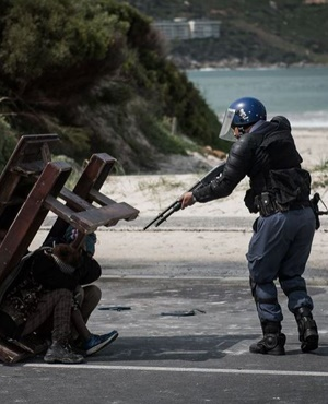 A policeman shoots a child during the Hout Bay protest. (Justin Sullivan)