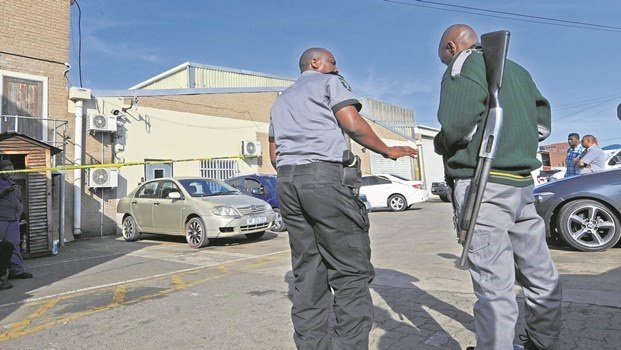 Fidelity security guards wait outside their premises in Greyling Street after a colleague was shot dead on Thursday afternoon.