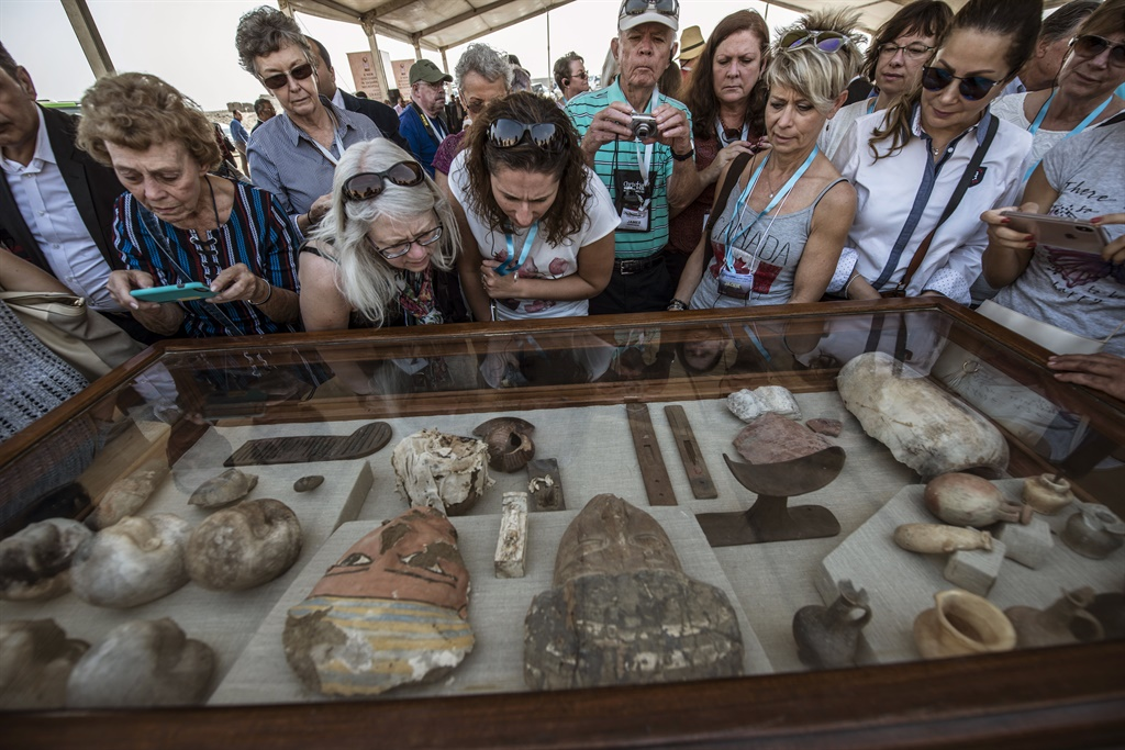 Diplomats and other viewers look at monuments displayed during a new discovery made by an Egyptian archaeological mission through excavation work at an area located on the stony edge of King Userkaf pyramid complex in Saqqara Necropolis, south of the capital Cairo. (AFP)