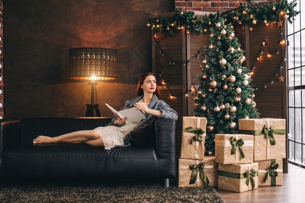 Woman sitting on the sofa near new year fir