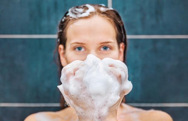 Woman holding loofah sponge in shower