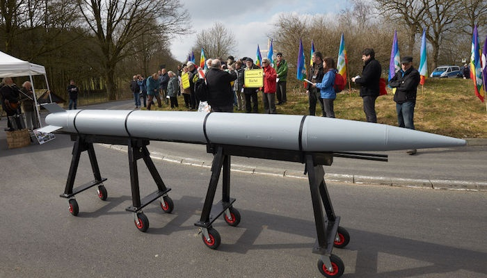 People take part in a protest with a model of a ro
