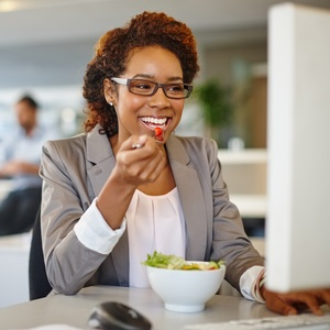 woman eating healthy at her desk