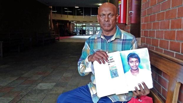 Steve Naidoo holds up a scrapbook on his daughter, Letisha Naidoo.