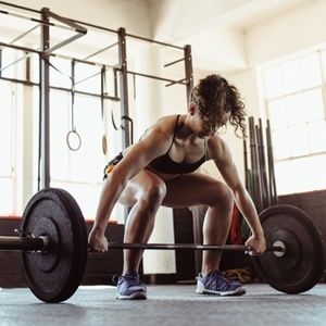 Healthy young woman lifting a barbell at the gym.