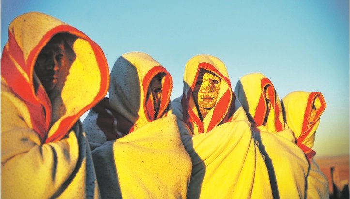 Initiates with white clay on their faces, covered in red and white blankets, during an initiation ritual. (Leon Sadiki, City Press)
