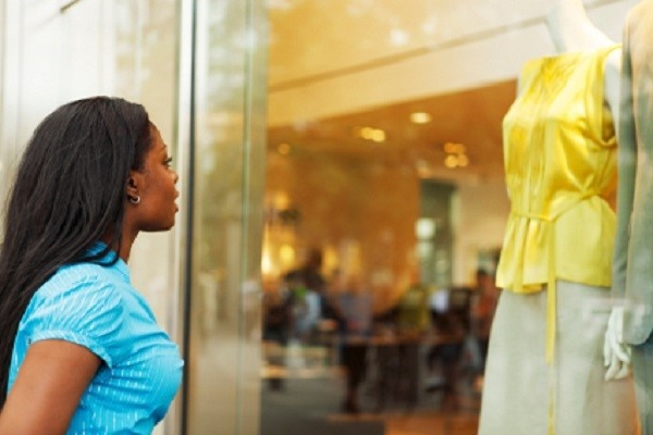 A woman looking at the clothes in a boutique windo