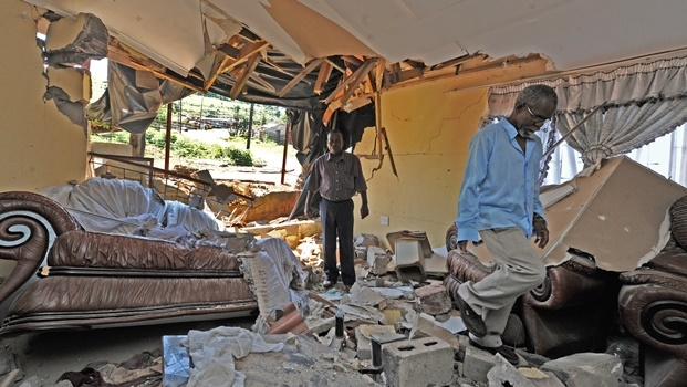 Pho (left) and Enock Zuma walk through the rubble that remained after a taxi crashed into their home in Haniville on Wednesday evening.