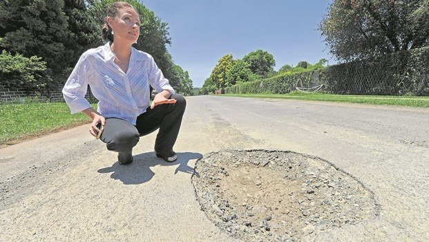 DA Ward 2 councillor in the uMngeni Municipality, Janis Holmes, next to a huge pothole on Wear Avenue in Howick. Since January, residents have been trying to lobby the municipality to attend to the road, which is full of deep potholes.
