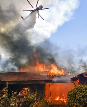 A a helicopter dumps water on a home as firefighters battle a wildfire called Canyon Fire #2 in Anaheim Hills in Anaheim, Calif. Wildfires whipped by powerful winds swept through Northern California sending residents on a headlong flight to safety through smoke and flames as homes burned. (Jeff Gritchen, The Orange County Register via AP, File)