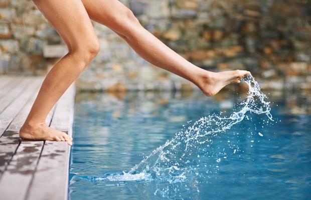 feet splashing in swimming pool
