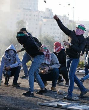 Palestinian protesters clash with Israeli troops near an Israeli checkpoint in the West Bank city of Ramallah. (Abbas Momani, AFP)