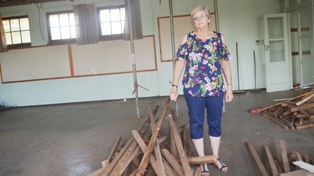 Pelham Senior Primary School principal Lorrel Wissing stands among some of  the wood that was removed from a classroom roof that had started caving in.