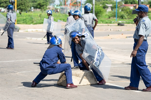 """Police officers remove tyres set by protesters during a """"stay-away"""" demonstration against the doubling of fuel prices in Emakhandeni township, Bulawayo.(Picture: AFP)<br />"""