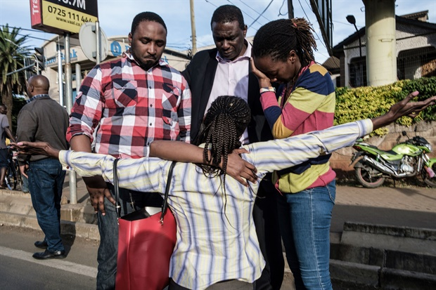A woman (behind the woman in front) is reunited with her