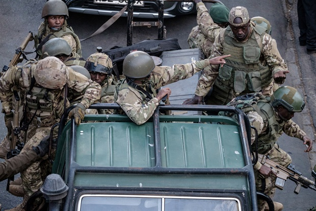 Kenyan security forces get out of a car after a blast