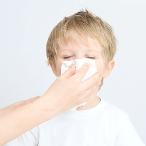 Child with whooping cough blows his nose