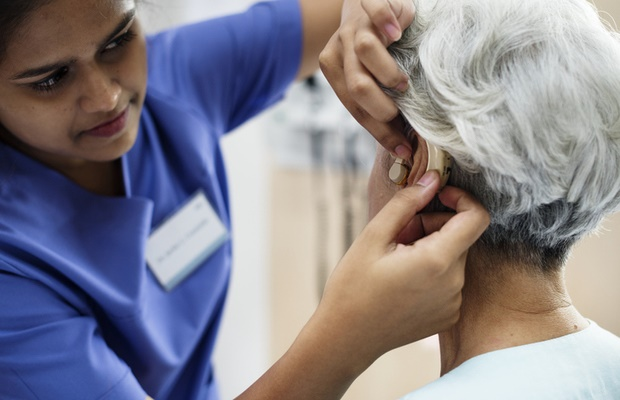 female doctor fitting patient with hearing aid