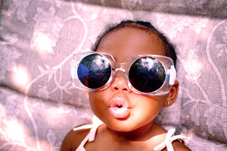 Baby girl sitting on lounge chair wearing sunglass