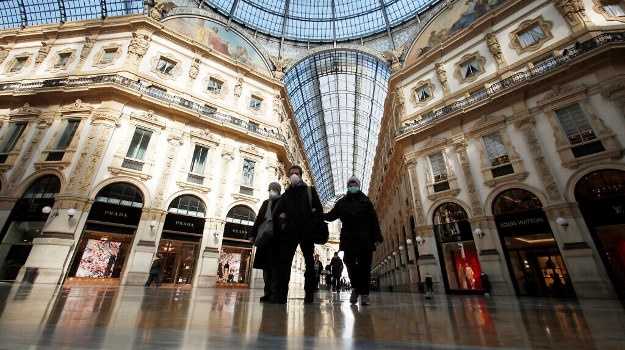 People wear masks as they walks inside Vittorio Emanuele II gallery, in downtown Milan, Italy, Sunday, March 8, 2020.  (AP Photo/Antonio Calanni)