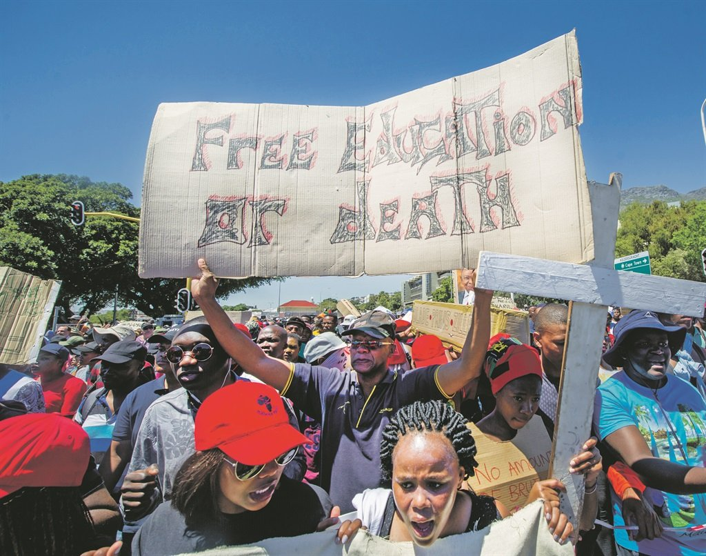 Thousands of protesters hold up signs as part of the #FeesMustFall campaign a few years back. (Gallo images / Jaco Marais)
